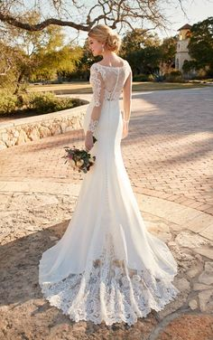 This Hollywood-inspired designer bridal gown from Essense of Australia features a romantic illusion lace bodice with clear beading and a rich crepe skirt that gives way to an heirloom-inspired lace train. The back zips up with ease under fabric-covered buttons.