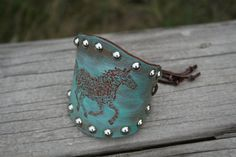 This unique leather cuff was hand stippled and stained. It has a sliding bead closure so it will fit any wrist.