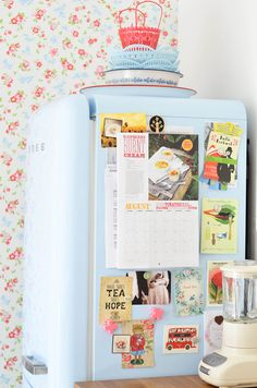 Baby blue Smeg decorated with vintage postcards and personal touches.