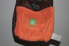 The fabric is a light corduroy  woodgrain with neon owls. The lining is orange fleece and I added fun iron ons.