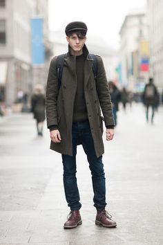 Den Look kaufen: https://lookastic.de/herrenmode/wie-kombinieren/mantel-pullover-mit-rundhalsausschnitt-jeans-stiefel-rucksack-schiebermuetze/551 — Olivgrüner Pullover mit Rundhalsausschnitt — Schwarzer Rucksack — Dunkelblaue Jeans — Olivgrüner Mantel — Olivgrüne Schiebermütze — Dunkelrote Lederstiefel