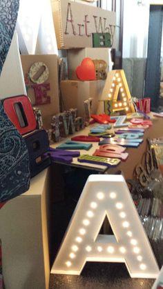 El puesto de Art Way en Mercado de Motores con letras y palabras en madera y cartón