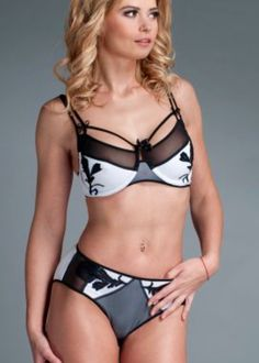 Strappy bra features lace appliques sewn on bra cups, see thru mesh details, hook and eye closure back, adjustable shoulder straps. White stretch jersey is made