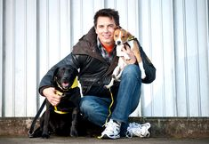 """John Barrowman Photos - Entertainer John Barrowman is seen out promoting the Dog Trust, spreading the message """"A dog is for life, not just for Christmas"""". Barrowman happily posed with pups Mouse the Black Labrador and Vincent the Jack Russell Terrier. - John Barrowman Promotes Dog Trust Dogs Trust, John Barrowman, Torchwood, Black Labrador, Jack Russell Terrier, Doctor Who, Pretty People, Actors & Actresses, Poses"""