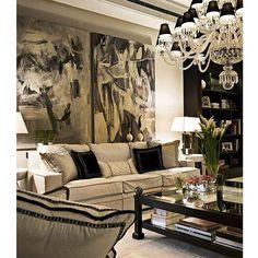Design Italiano numa sala cheia de luxo e requinte. Destaque para o lustre em cristal e as obras de arte na parede. Projeto Chiara Provasi