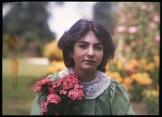 An Autochrome Of Etheldreda Janet Laing Daughter In A Garden, Holding A Brightly Coloured Bunch Of Pink Flowers,  1908