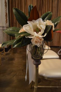 Magnolia blooms in hanging urns make an ideal statement as an aisle marker