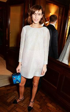 Alexa Chung in a silver dress, black flats, and blue clutch