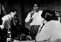 """France. Paris. Magnum office. 1947.From left to right: David SEYMOUR """"Chim"""", Werner BISCHOF (in the background) and Robert CAPA (pointing his finger)."""