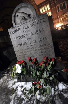 Roses lie near the original burial place of author Edgar Allan Poe Wednesday, Jan. 19, 2011 at Westminster Church and Cemetary in Baltimore. (AP Photo/Steve Ruark)