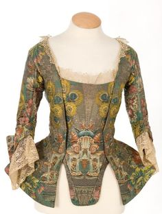 Jacket with winged cuffs, typical of 1730-40. Open with matching stomacher with lace tucker and at cuffs.