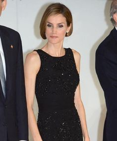"""Queen Letizia wore a little black dress by Felipe Varela. Letizia has repeated this sheath dress on numerous occasions and first wore it in June 2008. The cocktail dress features a sleeveless silhouette with tonal black sequins and a sash waist. Doña Letizia completed her look with familiar accessories. She carried a black satin clutch and wore her nude patent mary-jane pumps by Miu Miu. The Italian-made shoes have a 5"""" heel and feature an almond toe with a concealed 1"""" platform."""