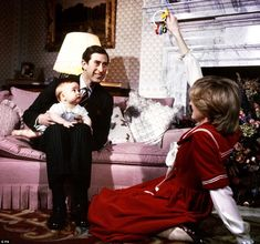 Prince Charles holding Prince William with Princess Diana on the floor getting William's attention.