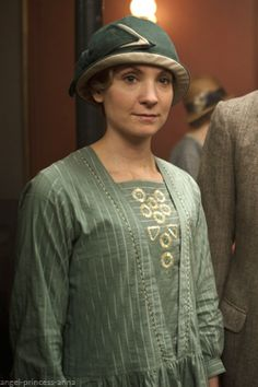 The always sensible, grounded downstairs beauty, Anna Bates, season 4, wearing a beautiful 1920's dropped waist,  sage green print frock w/ matching sold green over jacket, complimented w/ her cloche, straw hat banded w/ matching print material.  Stunning style.