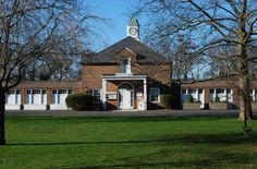 Mona's stables, which had room for 20 of the large cars of the era. In a bid to lower her taxes, she donated the complex to Evan's village. This is the village library, flanked by (unseen) various civic spaces, such as the village hall, a museum devoted largely to her, Boy and Girl Scouts, and a recreation center. She also donated about 30 acres of woods at the same time. This part of her estate had been called The Farm, as much of the produce consumed at the estate had been grown there. Historic Houses, You Know Where, Wishing Well, Town And Country, Stables, Gold Coast, Girl Scouts, Acre, Woods