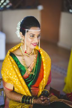 Green silk paithani saree with gold weaves and contrasting mustard shaalu, styled with thushi necklace and mohan maala.