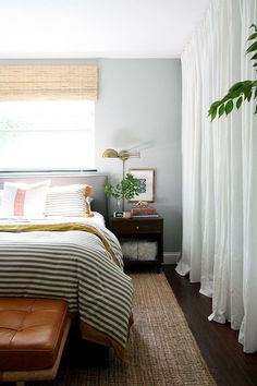 A bright and earthy bedroom with woven rug, stripped bedding, leather ottoman, and white curtains