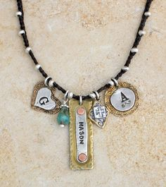 Silver beaded necklace with bronze sterling stamped charms. By Nelle and Lizzy