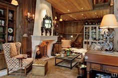 A living area occupies one end of the open main floor of the revamped Bucks County barn. The wing chair fabric is by Cowtan & Tout, and the stool is from Yale R. Burge Antiques.