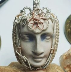 This wrap features a unique ceramic face wrapped in all Sterling silver and gold filled wire, with the exception of a seed of life pattern wrapped over the third eye which is made from copper in order to allow the energies to flow more freely!