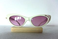 Vintage sunglasses in Cat Eye look. FREE WORLDWIDE SHIPPING!  Am not sure from what period these glasses are, but they look 70s. It has no brand name in it, but a stamp: France.  The material is hard plastic. The lenses inside are sunglass, non - prescription glass in a pinkish purple color. . The color is ivory white. Condition: used.  Dimensions: Total width: appr. 137 mm Temple: appr. 135 mm that bends at appr, 95mm, medium to a bit large sized.