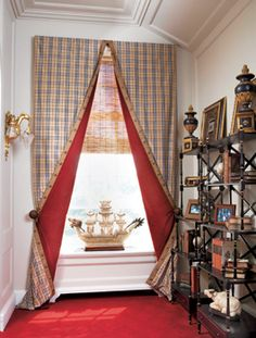 Designer Anne Lombardi-Rohrberg opted for an equestrian look in a study in the Caumsett show house, which was once owned by the retail magnate and horseman Marshall Field. She mounted flat Burberry-look taffeta panels on a narrow rod and flapped them back tent style to show off the unconventional red velvet lining. Rosettes on the British tan ribbon braiding on the leading edges of both sides echo the medallion holdbacks; a bamboo undershade controls light without blocking it completely.