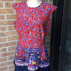 Vintage smock top handmade 1970s Peplum cotton handmade smock top.. Older piece..all cotton.. One button on back at neckline then sash to tie at waistline.. Also pockets on peplum.. Dutch floral patterned material.. Fits medium to extra large because of the way it's made.. Just cute Tops