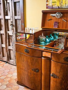 In this Mediterranean-inspired living space, a vintage wet bar has storage for supplies, including lemon zester, glasses and bottles of liquor.