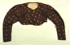 Die kurze spenzerartige Frauenjacke ist mit Abnähern und einem kleinen Schoß am Rücken versehen. Sie hat Keulenärmel, die an den Schultern angekraust sind und schlank zum Handgelenk auslaufen. Sie ist aus olivgrünem, gemustertem Kattun gefertigt und mit grobem, weißem Leinen gefüttert. An den Schultern und über der Brust ist sie wattiert. Handewitt #Jarplund