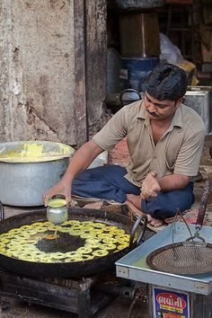 Roadside halwai (confectioner) making Jalebis.These are dipped in syrup for some time, after frying.