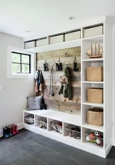 Lovely rustic cottage mudroom is equipped with cubbies holding vintage metal baskets beneath a white bench and shelves accented with tan baskets.