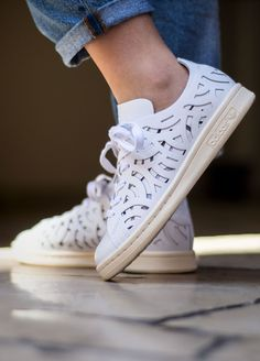White leather Stan Smith cut out sneakers from Adidas featuring a round toe, a lace-up front fastening, a brand embossed tongue, a branded insole, cut out details, a back embossed logo stamp and a flat rubber sole.
