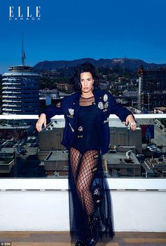 What a view: She posed on the top of a building in a sheer black outfit...