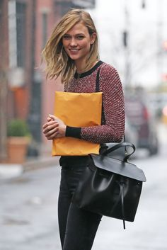 Karlie Kloss wears a red knit sweater, black jeans, and a Mansur Gavriel bag