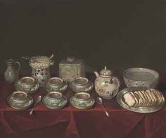 Porcelain tea cups, a teapot, a jug, sugar bowl, silver spoons and other objects on a draped table