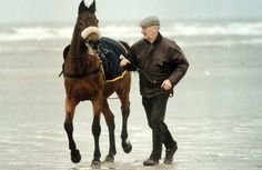 3 times Grand National winner Red Rum on the beach his trainer Ginger McCain.