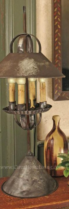 """What better way to complete your room than with our handsome 4 Bulb Table Lamp. Features a weighted base and Primitive Aged finish. 12"""" wide by 26"""" high."""