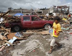 A boy carrying a plastic bottle of water walks past a car which slammed into damaged houses after super Typhoon Haiyan battered Tacloban city