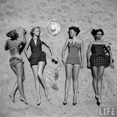 Four models showing off the latest bathing suit fashions while lying on a sandy Florida beach, 1950, by Nina Leen