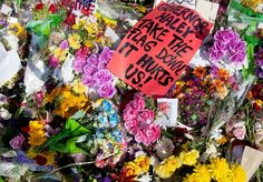 A sign calling for the removal of the Confederate flag from the South Carolina Statehouse grounds is laid in a pile of flowers left for the nine people killed at Emanuel AME Church.
