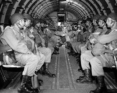 Paracaidistas americanos, pesadamente armados, se sientan dentro de un avión militar como ellos se elevan sobre Canal Inglés por el camino a la costa de francés de la Normandía para la invasión de Día de d Aliada de la fortaleza alemana durante la segunda Guerra Mundial, el 6 de junio de 1944.