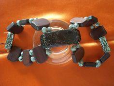 Pulseira dupla confeccionada em madeira, esferas de metal e detalhes em polímeros.