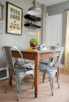 i love everything about this little dining space: the gray walls, the splashes of mustard yellow, the growing potter, the glasses hanging from walled shelves, the contrasting wooden table and aluminum chairs, the framed slogan...its me