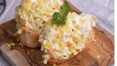En primer lugar,picamos bien los palitos de surimi o chakay lo mezclamos con la mayonesa. Salpimentamos y reservamos. A continuación, cortamos rodajas finas de pan y ponemos esta mezcla encima. Por último, rallamos los huevos cocidos por encima. Emplatamos y servimos con unas hojas de perejil rizado.