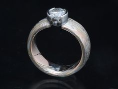 A diamond set in a domed comfort fit etched ring 6.5mm wide in 18K yellow gold, 14K palladium white gold, 14K red gold and sterling silver in tight wood grain pattern with a platinum open half bezel setting.