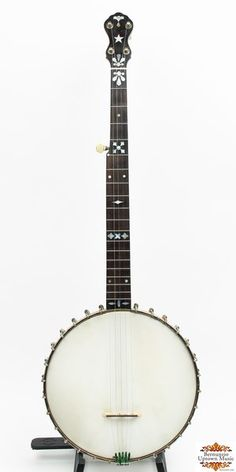 """From the banjo hay days of the 1890s comes this electric model. The electric was Fairbanks flagship model the the scallopped metal tonering that was introduced in 1890. The addition of the ring to the rim gave the banjo its """"electrifying"""" sound.... this eventually evolved into the fabled """"Whyte Laydie"""" model. This particular model features a mahogany neck with inlayed pearl """"tear drops"""" in the fingerboard and peghead. What sets this particular banjo apart is the unusual rim and neck…"""