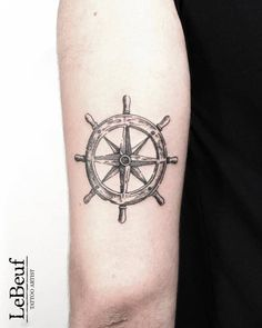 Compass ship wheel tattoo on the back of the left arm.