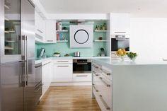 belle cuisine blanche avec une crédence en vert menthe et déco d'agrumes