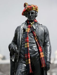 Statue of Robert Burns in George Square, Glasgow, with a tartan bonnet and scarf
