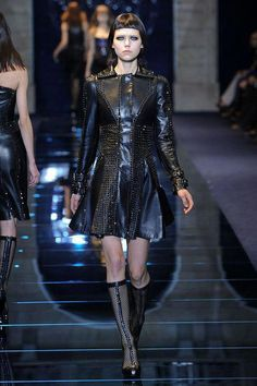Versace Fall 2012 Black leather jacket that comes in at waist and flares  out and drapes beautifully falling just mid-thigh. The studding details  flow ... 6bc7f56e2f9